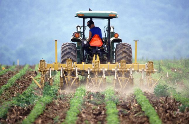 Farmer_and_tractor_tilling_soil